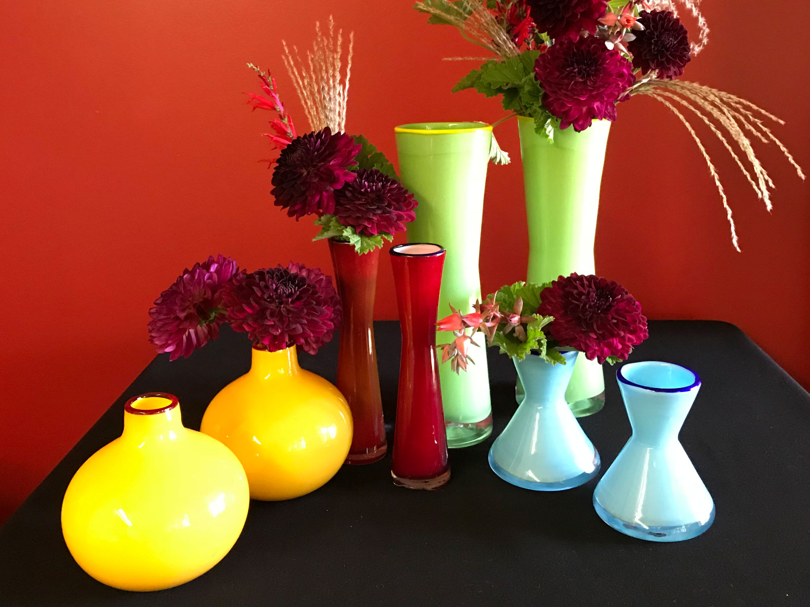 Sets of orange, red, green and blue vases with purple flowers in each one