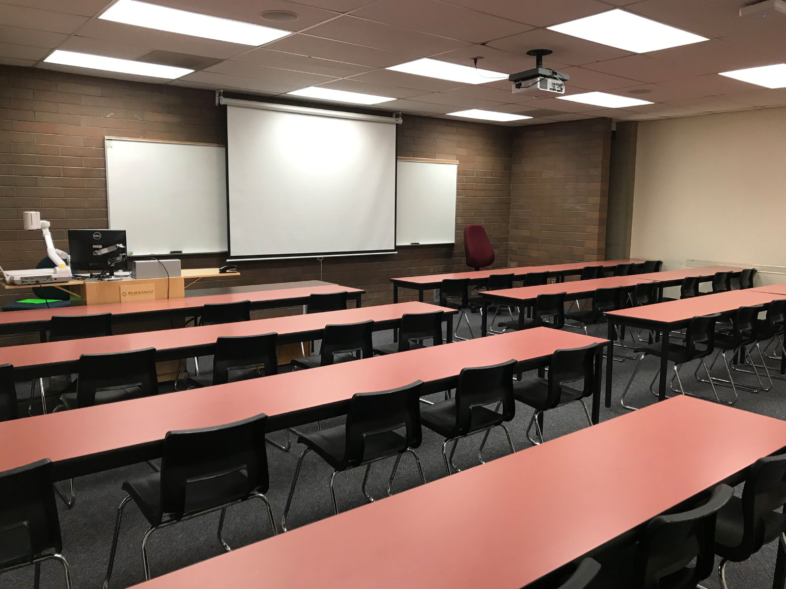Rows of red tables and a podium in an Oregon CIty classroom with a projector screen against a brick wall