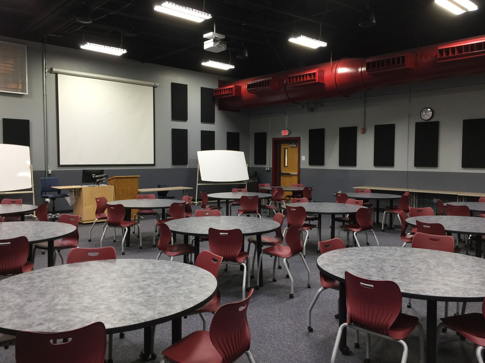 Many tables and chairs in front of a projector display in classroom W108B on the WIlsonville campus