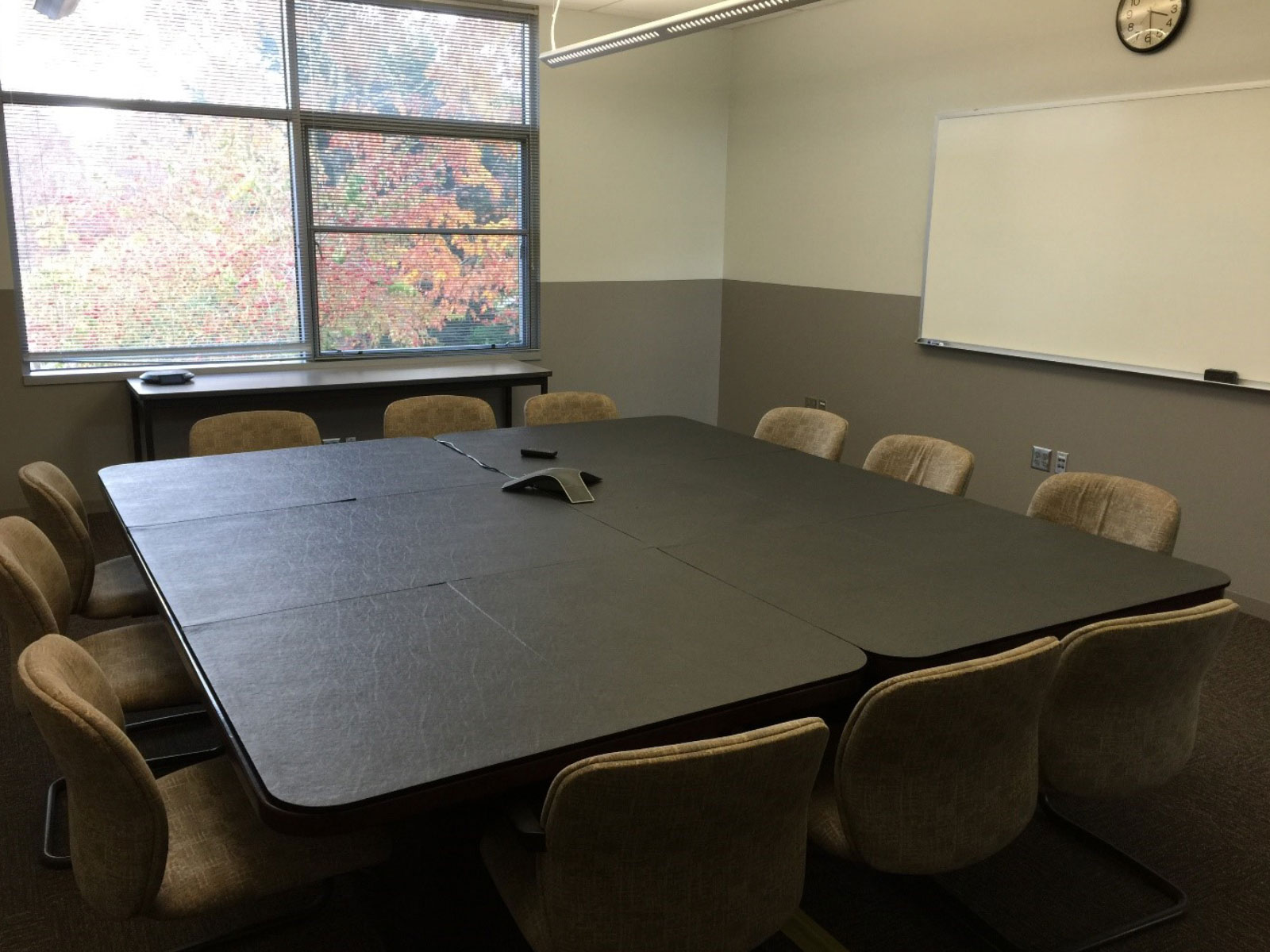 Conference room with 12 chairs and a table with center phone, white board on the wall and window in classroom W207 on the Wilsonville campus
