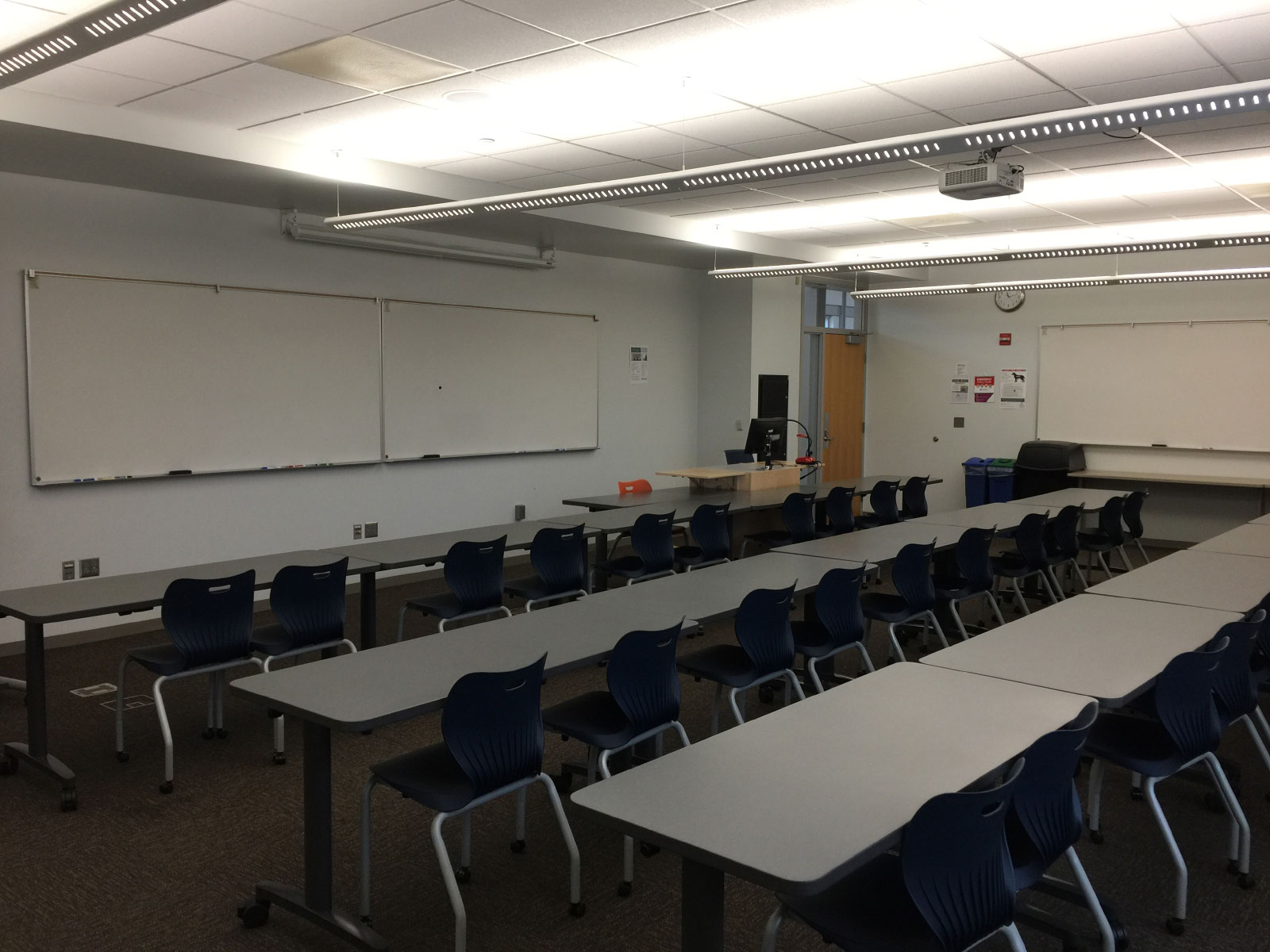 Rows of blue chairs and tables in front of a podium and white board in classroom W210 on the WIlsonville campus