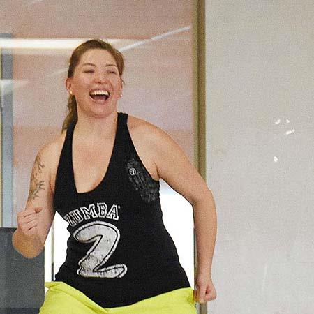 "woman exercises wearing shirt that says ""zumba"""